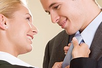 Side profile of a businesswoman adjusting a businessman´s tie
