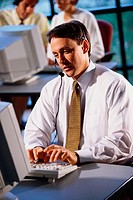 Man with headset looking at computer
