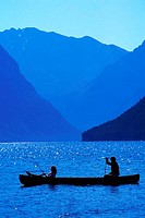 Silhouetted canoeists on lake