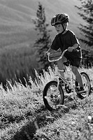 Boy riding mountain bike in woods