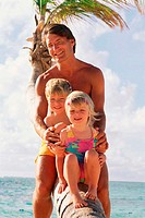 Father sitting with young children on palm tree at beach