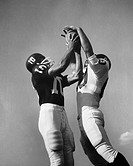 Two football players jumping for ball at same time
