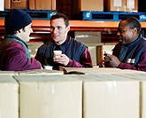 Three men in warehouse taking break, close-up