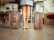Businesswoman standing by leather suitcases, indoors,  low section