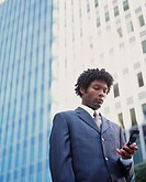 Businessman outside of office building looking down at mobile phone