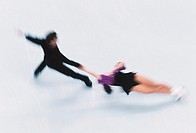 Couple figure skating on ice, elevated view (blurred motion)