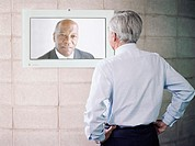 Mature businessman having video conference with colleague