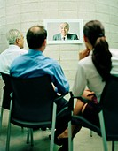 Business executives watching screen during video conference