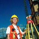 Woman wearing hardhat, standing next to surveying equipment, portrait