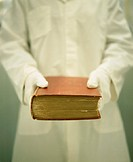 Woman in white gloves holding book, mid section (focus on book)