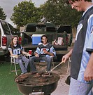 Sports fans drinking and using barbecue grill at tailgate party