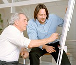 Mature man using drawing board in front of man
