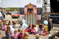 Group of children sitting on the floor, watching a Punch and Judy show, Salcombe, England. UK.