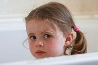 3 year old girl in the bath looking very seriously into the camera