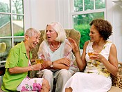 Three mature women talking and laughing, holding glasses of wine