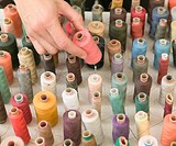 Woman picking up pink reel of thread from assorted reels, close-up