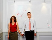 Business couple holding hands in front of love heart on white board