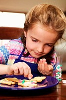 Girl (7-9) decorating biscuits on plate, close-up