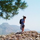 Woman with backpack on rocky cliff edge using mobile phone, side view