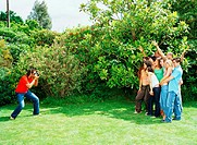 Group of friends having photograph taken by man, outdoors