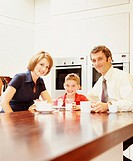 Parents and son (6-8) at breakfast counter, portrait