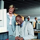 Businesswoman standing by businessman at desk, smiling
