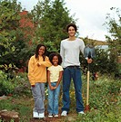 Young man holding shovel with kids (7-10) in garden, smiling, portrait
