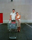 Young couple embracing by shopping trolley, portrait