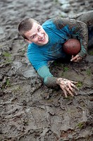 Young man lying on muddy field, holding football, portrait