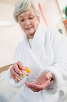 Senior woman holding prescription pill bottle (focus on hand)