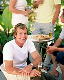 Group of adults at cocktail party (focus on man holding beer)