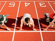 Teenage boy at starting block in track and field race, elevated view