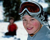 Boy (10-12) wearing ski goggles, smiling, portrait, close-up