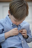 Boy (4-6) buttoning shirt, close-up