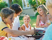 Family at table having lunch outdoors, smiling