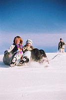 Three teenagers (13-15) in snow, two girls riding inner tube down hill