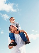 Boy (4-6) sitting on man´s shoulders, outdoors, low angle view