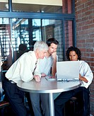 Three businessmen at table looking at laptop computer screen