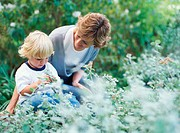 Mother kneeling by son (2-4) playing with plant, outdoors