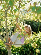 Girl (5-7) climbing tree, hanging from branch, smiling