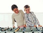 Girl (7-9) and boy (8-10) playing table football, smiling