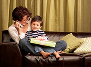 Mother talking on cell phone, son (3-5) sitting on lap, holding gift