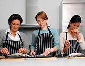 Three women in kitchen gutting fish on chopping boards