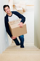 Mature man walking up stairs, carrying cardboard box, elevated view