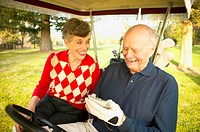 Senior couple sitting in golf cart, man writing on score card, smiling