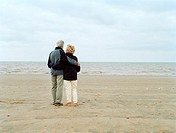 Senior couple standing on beach with arms around each other, rear view