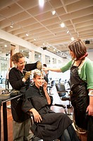 Young woman talking on cell phone while two hairdressers dye her hair