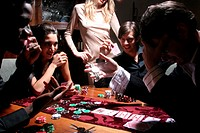 Five young adults playing poker, one man betting wristwatch