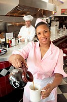 Waitress pouring cup of coffee in diner, cook in background, portrait