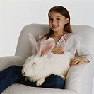 Girl (7-9) on armchair with white rabbit, smiling, portrait